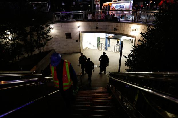 Police officers stand at the entrance to a closed subway station during a power outage Saturday (AP Photo/Michael Owens)