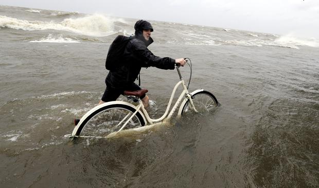 Tyler Holland guides his bike through the water as winds from Tropical Storm Barry push water from Lake Pontchartrain (AP Photo/David J. Phillip)