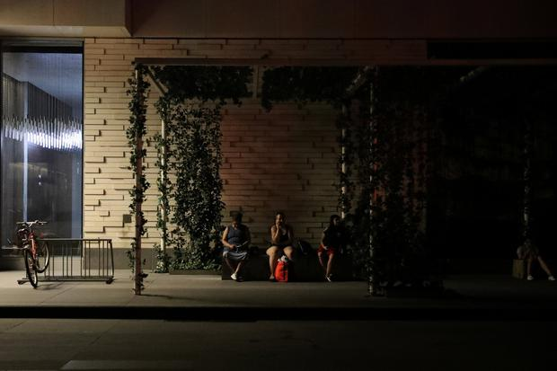 People sit outside their residential building near Times Square, as a blackout affects buildings and traffic during widespread power outages in Manhattan. Photo: REUTERS/Jeenah Moon