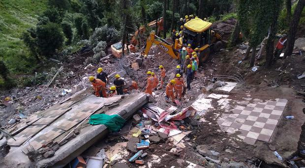 Rescuers of India's National Disaster Response Force (NDRF) look for survivors after a three-story building collapsed in monsoon rains near the town of Solan, a hilly area 310 kilometers (195 miles) north of New Delhi. Photo: AP Photo