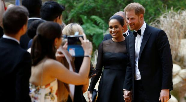 Britain's Prince Harry and Meghan, Duchess of Sussex pose for pictures as they attend the European premiere of