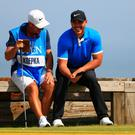 Brooks Koepka and his caddie Ricky Elliott share a joke during a practice round prior to the 148th Open Championship held on the Dunluce Links at Royal Portrush Golf Club. Photo: Mike Ehrmann/Getty Images