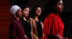 Hitting back: From left, Ilhan Omar, Alexandria Ocasio-Cortez and Rashida Tlaib look on as Ayanna Pressley speaks. Photo: AFP/Getty Images