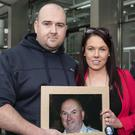 Seeking damages: Robert and Michelle Ryan, with a photo of their murdered father, Bobby. Photo: Collins Courts
