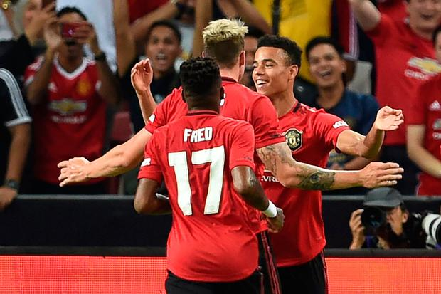 Manchester United's Mason Greenwood (back R) is congratulated by teammates after scoring during the International Champions Cup football match between Manchester United and Inter Milan in Singapore on July 20, 2019. (Photo by Roslan RAHMAN / AFP)ROSLAN RAHMAN/AFP/Getty Images