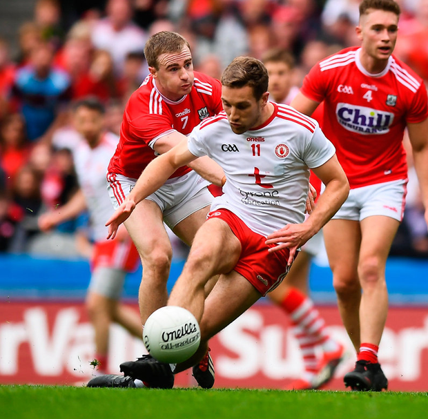 Tyrone's Niall Sludden is fouled by Mattie Taylor of Cork which resulted in referee Maurice Deegan awarding the Ulster side a penalty, which was subsequently coverted by Peter Harte. Photo: David Fitzgerald/Sportsfile