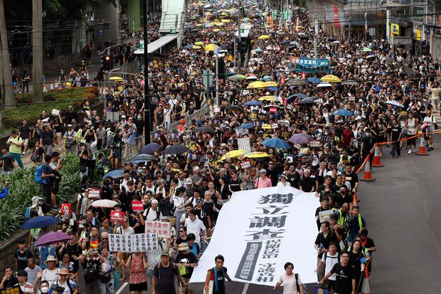 Protesters hold a white banner which reads