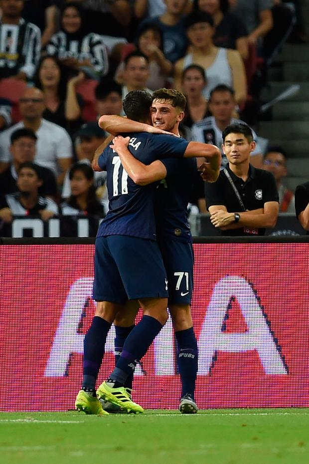 Tottenham Hotspur's Erik Lamela (L) is congratulated by teammate Troy Parrott