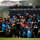 Open Season: Shane Lowry soaks it all in as he and his caddie Brian 'Bo' Martin walk up the 18th, pursued by hordes of delighted supporters. Photo: Sportsfile