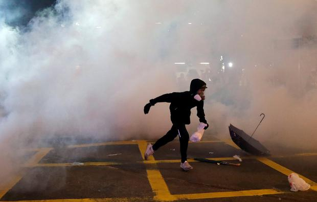 Fog: A protester runs through tear gas fired by police during the trouble in Hong Kong. Photo: REUTERS/Tyrone Siu