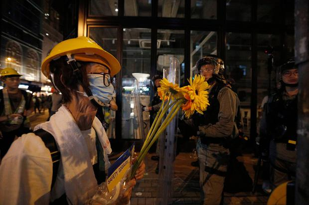 An elderly man offers flowers to police asking them not to harm the young protesters. Photo: AP Photo/Bobby Yip