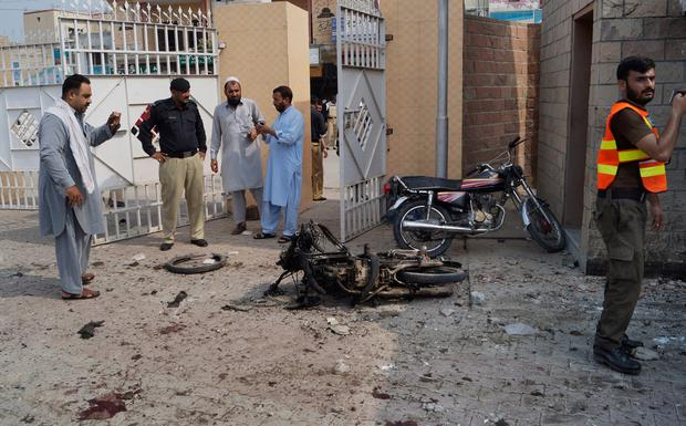 Pakistani security officials examine the site of a bombing on an entrance of a hospital in Dera Ismail Khan, Pakistan. Photo: AP Photo/Ishtiaq Mahsud
