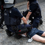 Police restrain one of the attackers during the march. Photo: Magda Bogdanowicz/via REUTERS