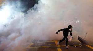 An anti-extradition demonstrator runs away from tear gas, after a march to call for democratic reforms, in Hong Kong REUTERS/Tyrone Siu