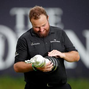 Shane Lowry inspects the Claret Jug on the 18th green. Photo: Reuters