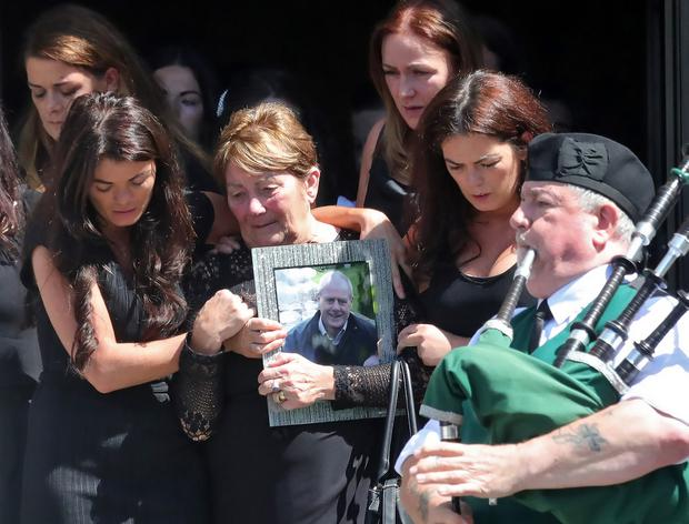 Mourners carry a picture of John Hutch after his funeral at the Church of the Holy Family, Aughrim Street this morning ..Picture Colin Keegan, Collins Dublin