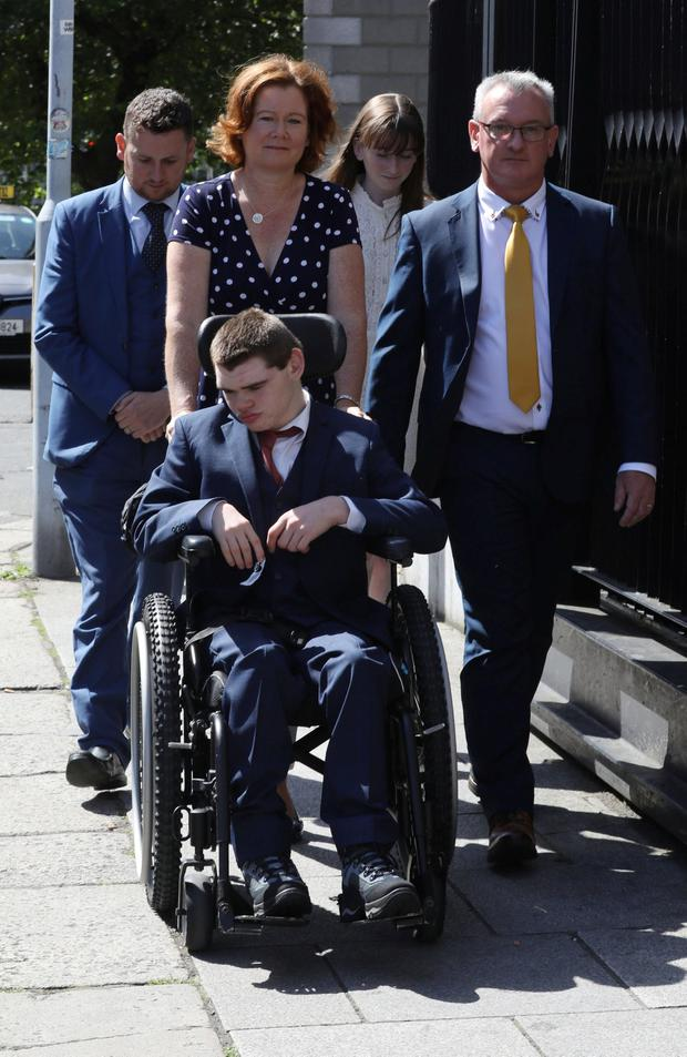 23/7/2019 (In Wheelchair) Sam Forde, of Glenview Park, Grange, Co. Sligo pictured leaving the Four Courts - with his family, Deborah (mum), Des (dad) and sister, Hannah and solicitor, David O Malley (back of pic - left) after the High Court approved a settlement offer of €10.5Million.Pic: Collins Courts