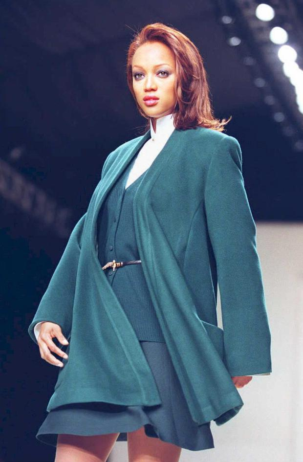 Model Tyra Banks presents a malachite wool wrap coat with matching wool ribbed cardigan and flip skirt over a white cotton trapunto collar shirt in the Ellen Tracy Fall 1995 fashion show in New York 04 April. AFP PHOTO