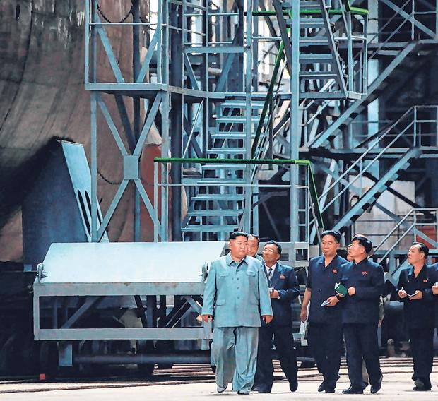 Inspection: Kim talks to reporters during his visit to the submarine at an undisclosed location. Photo: AFP