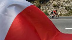 Ireland's Nicolas Roche passes by a French national flag flying on the roadside. Photo: AFP/Getty Images