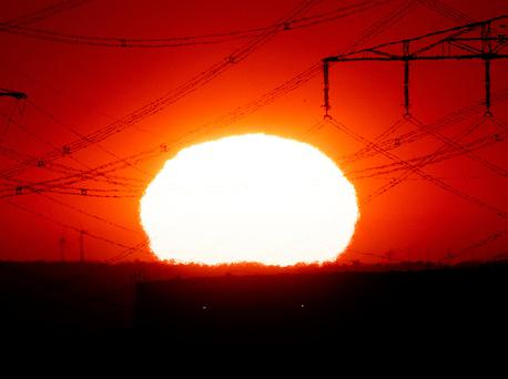 The sun rises near power lines in Frankfurt, Germany, Wednesday, July 24, 2019. A heatwave struck large parts of Europe. (AP Photo/Michael Probst)