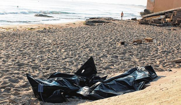 Tragedy: Bags containing the bodies of migrants who died after their boat capsized near Libya lie on the beach. Photo: Ayman al-Sahili/Reuters
