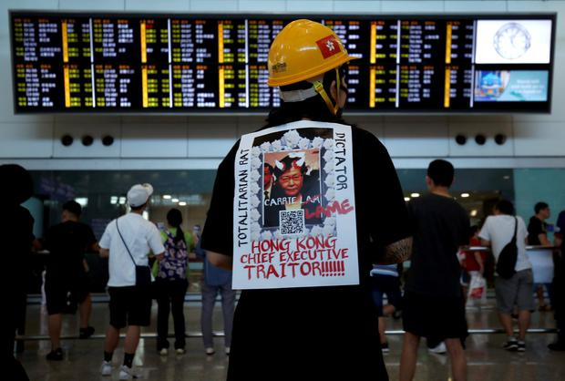 A demonstrator wears a placard during a protest against the recent violence in Yuen Long, at Hong Kong airport. Photo: Edgar Su/Reuters