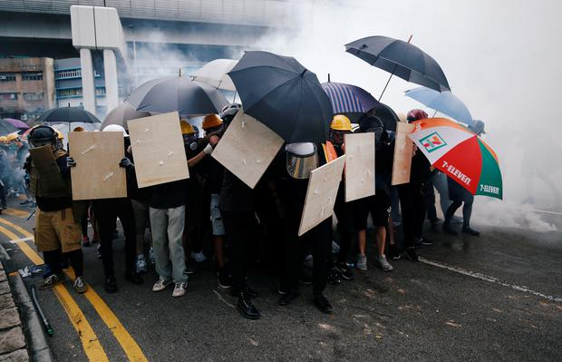 Demonstrators use shields and umbrellas to protect themselves during a protest against the Yuen Long attacks in Yuen Long, New Territories, Hong Kong, China July 27, 2019. REUTERS/Edgar Su