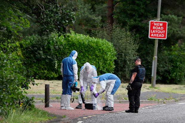 An ammunition technical officer and forensic officers in Tullygally Road, Craigavon, Co Armagh after an explosive device used by dissident republicans in a failed bid to kill police officers was discovered. Brian Lawless/PA Wire