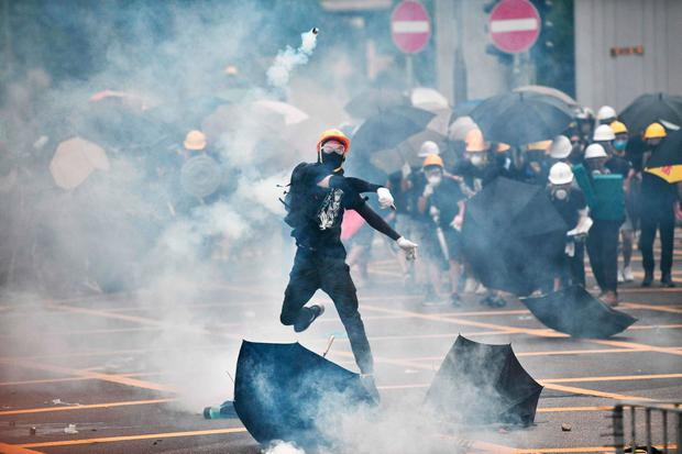 RETURN TO SENDER: A protester throws tear gas back at police during a demonstration in Hong Kong yesterday. Photo: Anthony Wallace/AFP/Getty Images