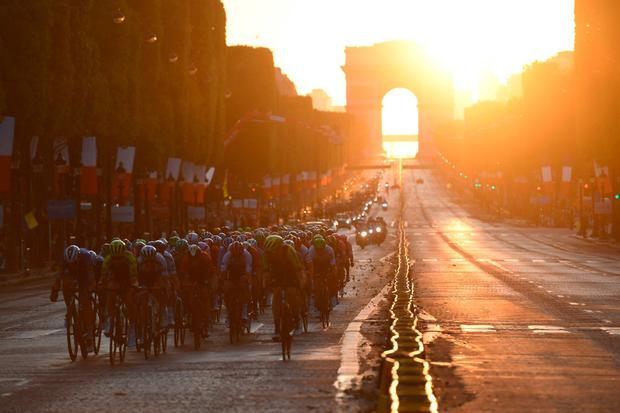 Cyclists ride down the Champs Elysees with the Arc de Triomphe in the background on the final stage of the Tour De France. Photo: Martin Bureau/AFP/Getty Images