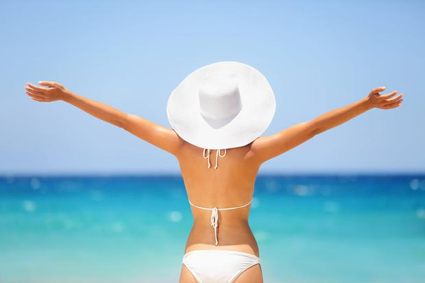 Beach summer holidays woman in happy freedom concept with arms raised out in happiness. Woman model wearing white bikini and beach hat on Big Island, Hawaii.