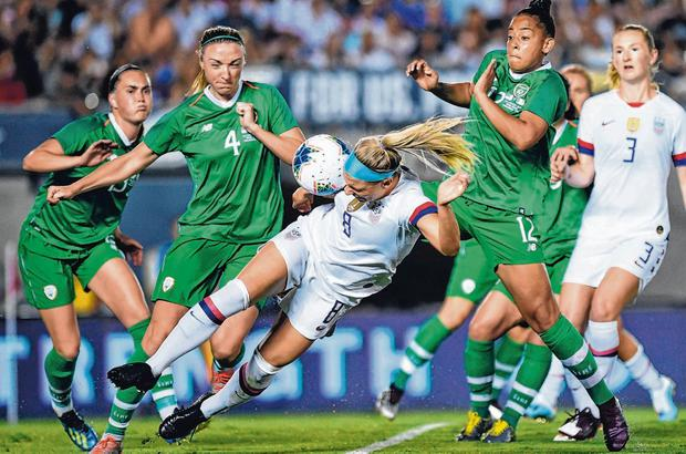 Julie Ertz of USA heads the ball away from a corner despite the attention of Republic of Ireland players Louise Quinn (4) and Rianna Jarrett. Photo: Cody Glenn/Sportsfile