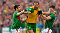 Donegal's Michael Murphy is held by Chris Barrett (left) and Eoin O'Donoghue of Mayo as Aidan O'Shea lies injured holding his face. Photo by Brendan Moran/Sportsfile