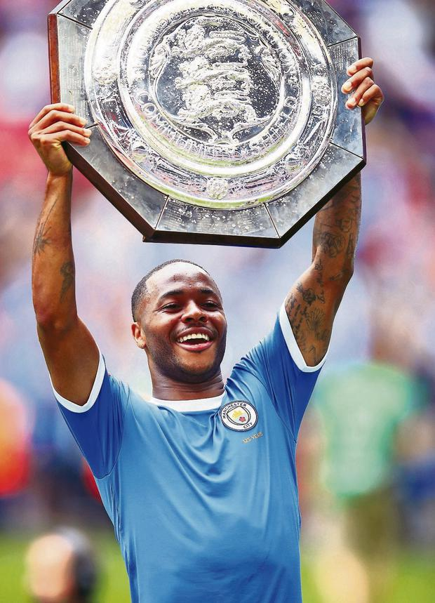 Raheem Sterling lifts the trophy after his side's Community Shield victory. Photo: Adam Davy/PA Wire