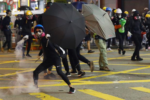 Street battle: A masked protester – with others shielded by umbrellas – hurls back a tear gas canister at police in Hong Kong. Photo: Reuters/Kim Kyung-Hoon