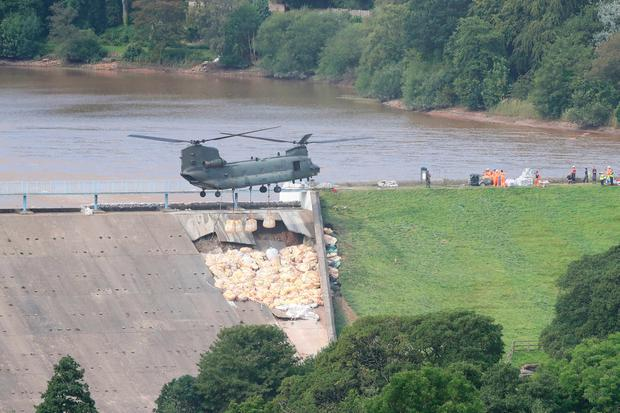 A military helicopter was used to drop sandbags into the dam. Photo: Peter Byrne/PA Wire