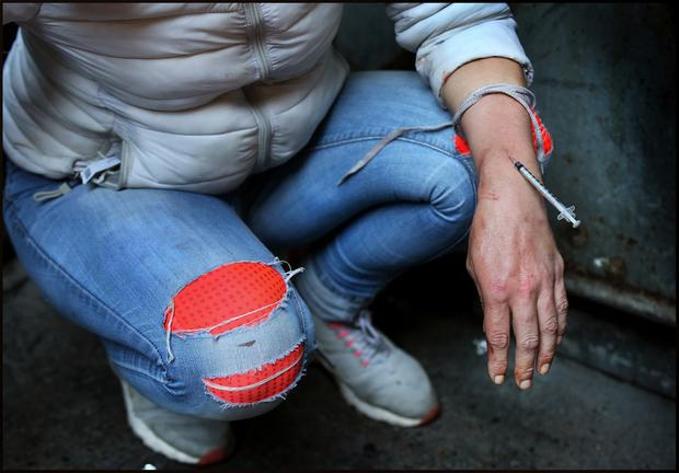 A young woman injecting Heroin into her arm at Harbour Court, a laneway which runs between Abbey Street and Eden Quay. Pic Steve Humphreys