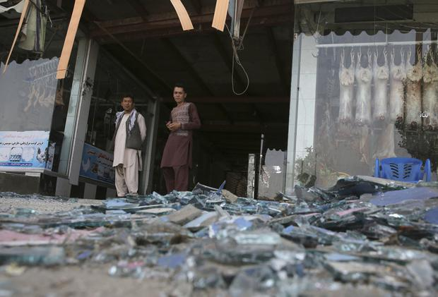 Afghans stand near a damaged shop after an explosion in Kabul, Afghanistan Photo: AP Photo/Rafiq Maqbool