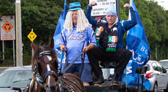 Horseplay: Christopher Gunning drives his American cousin Tyrone Grehan to Dublin Airport in a horse and cart draped in Dublin flags after an emotional trip back to Ireland. Photo: Owen Breslin