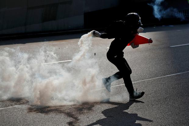 A protester prepares to throw a tear gas canister fired by riot police as protesters face off with police near the Legislative Council building and the Central Government building in Hong Kong, last Monday. AP Photo/Vincent Thian