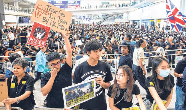 Warnings: Placards were held up to tell incoming travellers of the police use of tear gas during protests. Photo: Reuters