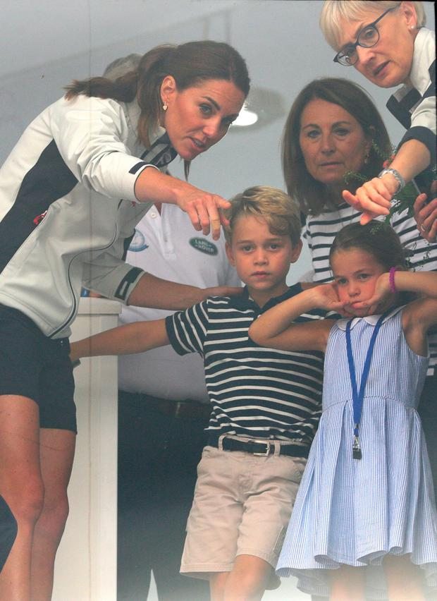 The Duchess of Cambridge with Prince George and Princess Charlotte look through a window at the prize giving after the King's Cup regatta at Cowes on the Isle of Wight