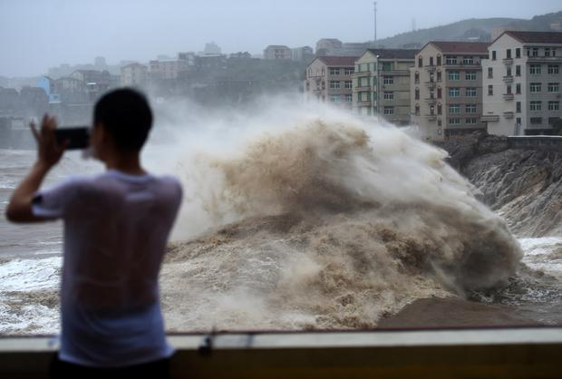 In this Aug. 9, 2019, photo released by Xinhua News Agency, a man uses his mobile phone to record waves crashing on the shore as typhoon Lekima approaches the Shitang Township of Wenling City in eastern China's Zhejiang Province. Typhoon Lekima stuck the coast south of Shanghai, knocking down houses and trees. (Han Chuanhao/Xinhua via AP)