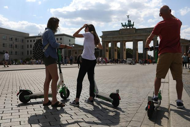 Uneven market: Lime electric scooter users in Berlin. Europe's cobbled streets have posed problems for some operators. Photo: Krisztian Bocsi/Bloomberg
