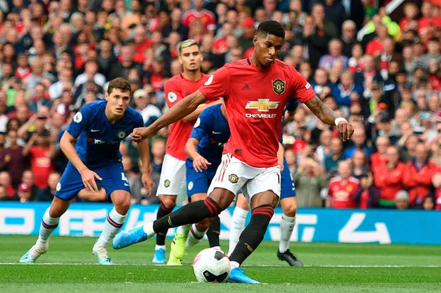 Manchester United's English striker Marcus Rashford (C) shoots to score from the penalty spot for the opening goal. Photo: Getty Images