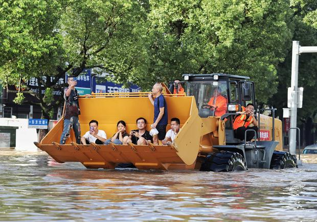 Rescue vehicle: An improvised use of a bulldozer helps rescuers evacuate people from their homes in Zhejiang. Photo: Reuters/Stringer