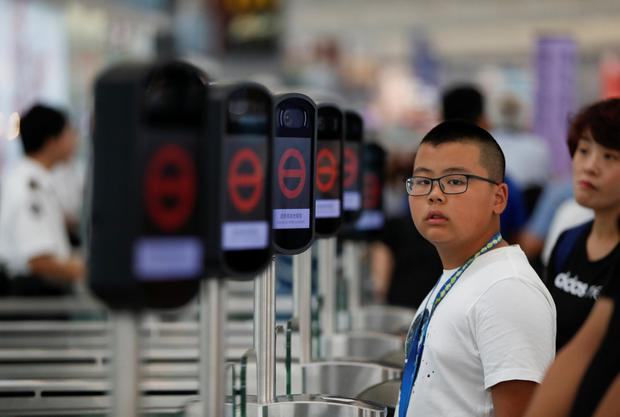 People are seen next to the temporary closed security gates as anti-extradition bill demonstrators protest at the departure hall of Hong Kong Airport, China August 12, 2019. REUTERS/Issei Kato