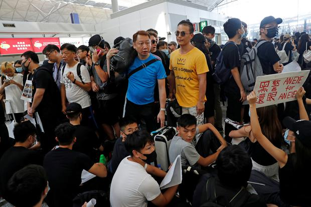 People try to go through anti-extradition bill protesters during a mass demonstration after a woman was shot in the eye during a protest at Hong Kong International Airport, in Hong Kong, China August 12, 2019. REUTERS/Tyrone Siu