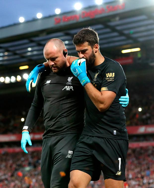 Liverpool goalkeeper Alisson (right) leaves the pitch after picking up an injury
